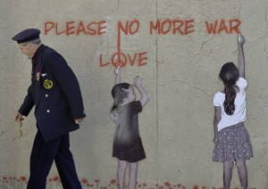 British D-Day veteran Butler stands near a wall mural in Arromanches-les-Bains on the Normandy coast