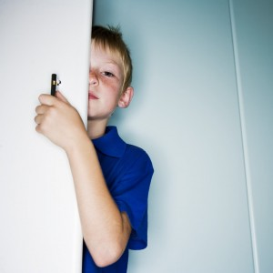 Boy Hiding Behind Door --- Image by © Royalty-Free/Corbis